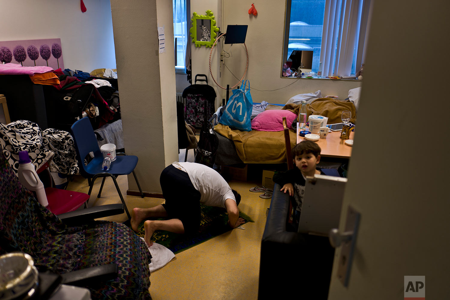 In this Wednesday, June 28, 2017 photo, refugee Hani Nashed, 53, from Aleppo, Syria, offers prayers while his young neighbour Lith Mashhadi, 3, a Syrian refugee from Aleppo, peeks on, at Hani's room in the former prison of Bijlmerbajes, in Amsterdam, Netherlands. (AP Photo/Muhammed Muheisen)
