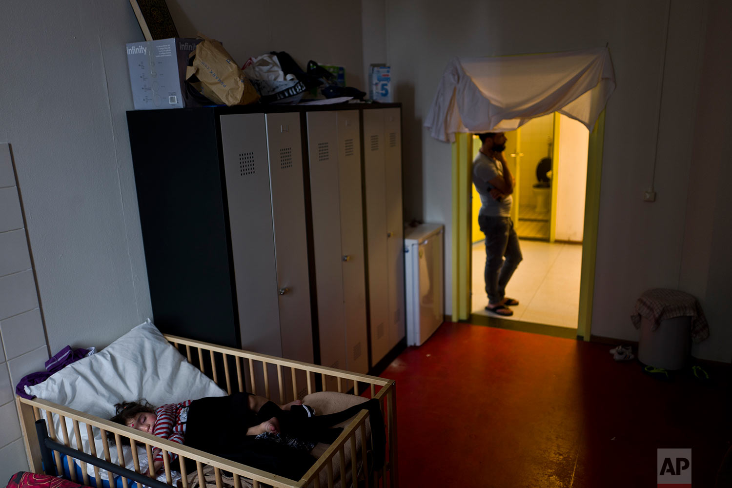 In this Tuesday, June 27, 2017 photo, 20-month-old Naya Mahmoud, a refugee from Aleppo, Syria, sleeps in a crib inside her family's room at the former prison of Bijlmerbajes in Amsterdam, Netherlands. (AP Photo/Muhammed Muheisen)