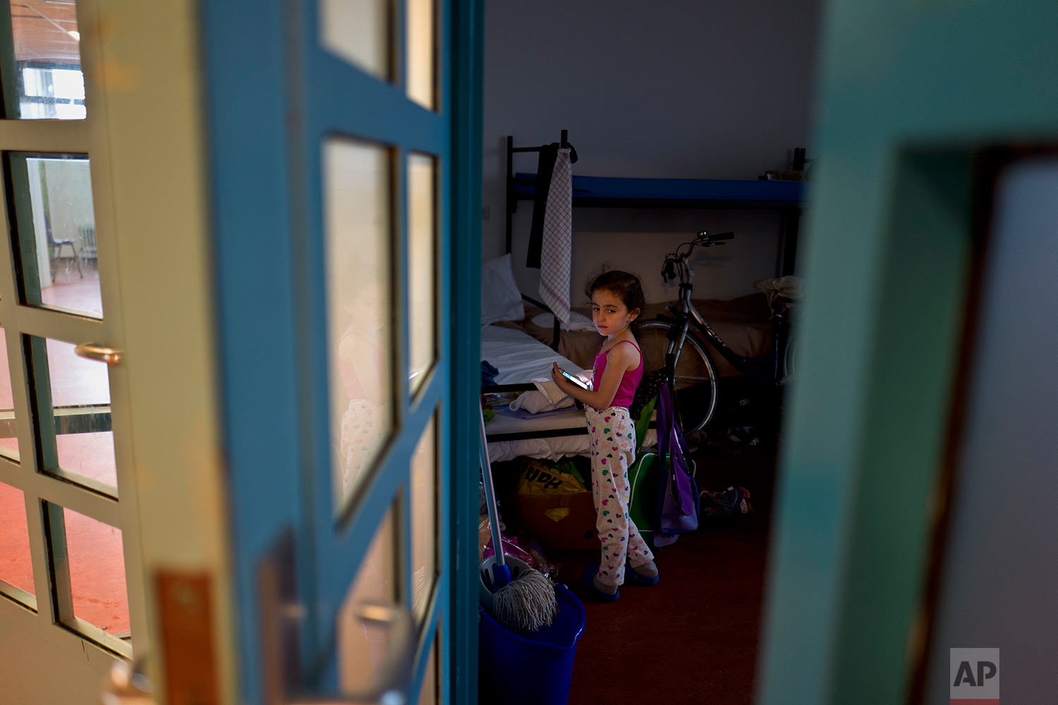 In this Friday, June 30, 2017 photo, refugee Sandi Yazji, 5, from al-Hasaka, Syria, holds a mobile phone while standing inside her room at the former prison of Bijlmerbajes in Amsterdam, Netherlands. (AP Photo/Muhammed Muheisen)