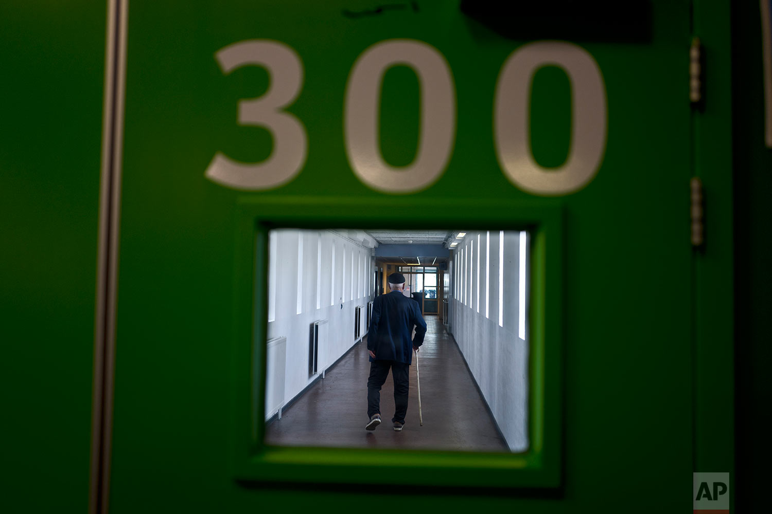 In this Wednesday, July 12, 2017 photo, an elderly Iraqi refugee man walks back to his room through a corridor of the former prison of Bijlmerbajes in Amsterdam, Netherlands. (AP Photo/Muhammed Muheisen)
