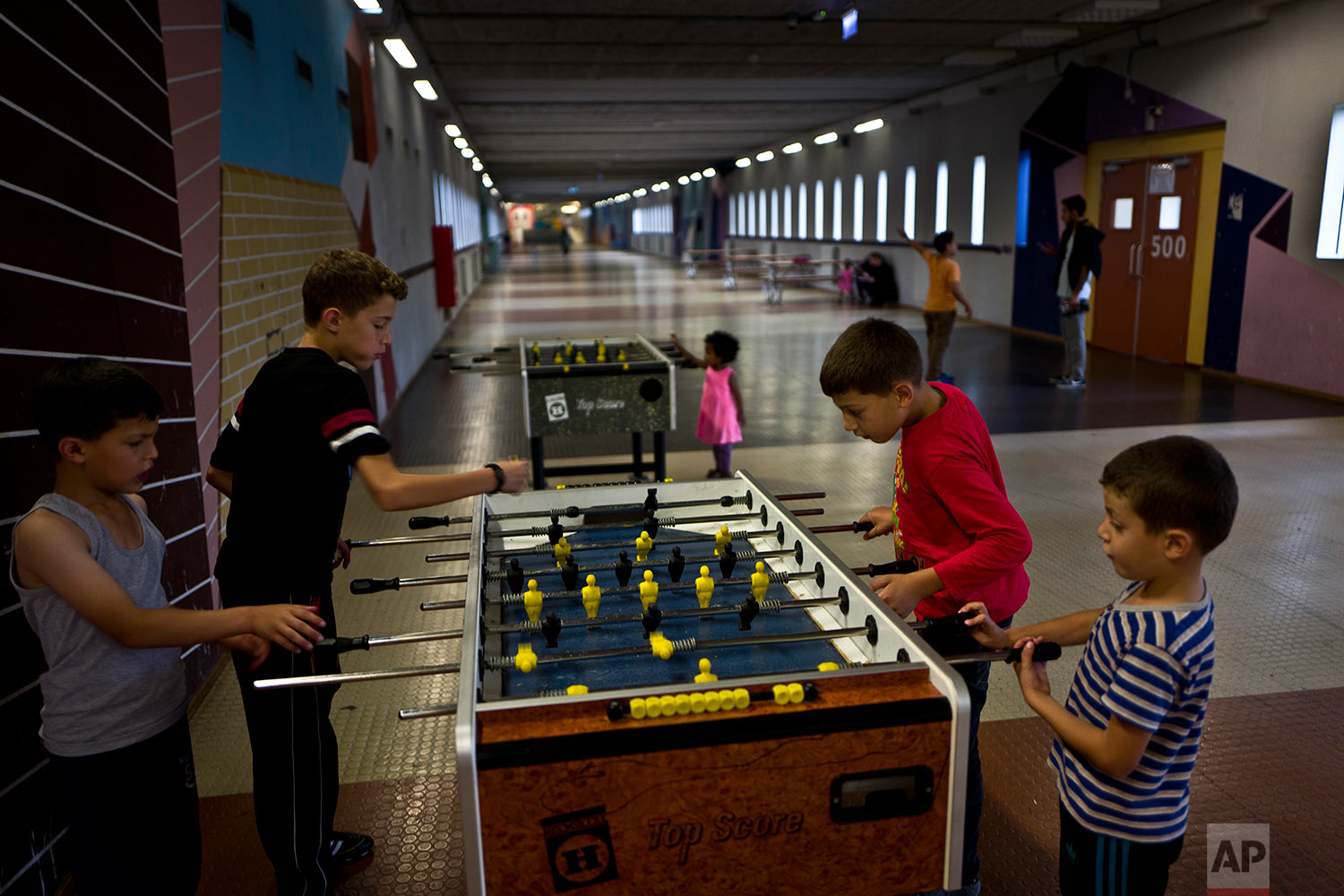 In this Monday, June 26, 2017 photo, refugee brothers from Baniyas, Syria, from right, Izzeldein Moustafa, 6, Abdulrahman, 10, Ahmad, 12 and Amir, 8, play table foosball in a corridor known as Kalverstraat, referring to a busy shopping street in Amsterdam, at the former prison of Bijlmerbajes in Amsterdam, Netherlands. (AP Photo/Muhammed Muheisen)