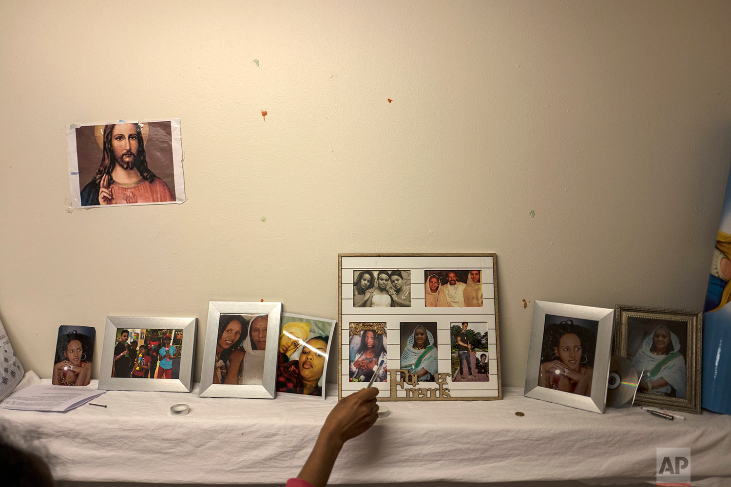 In this Sunday, July 9, 2017 photo, Eritrean migrant Ksanet Goitom, 23, points at pictures that she brought with her from Eritrea showing family members and friends, displayed at her room in the former prison of Bijlmerbajes in Amsterdam, Netherlands. (AP Photo/Muhammed Muheisen)
