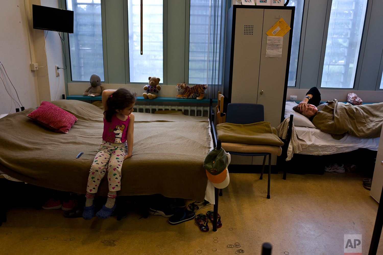 In this Friday, June 30, 2017 photo, refugee Nadia Gattas, 82, from Deir el-Zour, Syria, right, lies on a bed in her room in the former prison of Bijlmerbajes in Amsterdam, Netherlands. (AP Photo/Muhammed Muheisen)