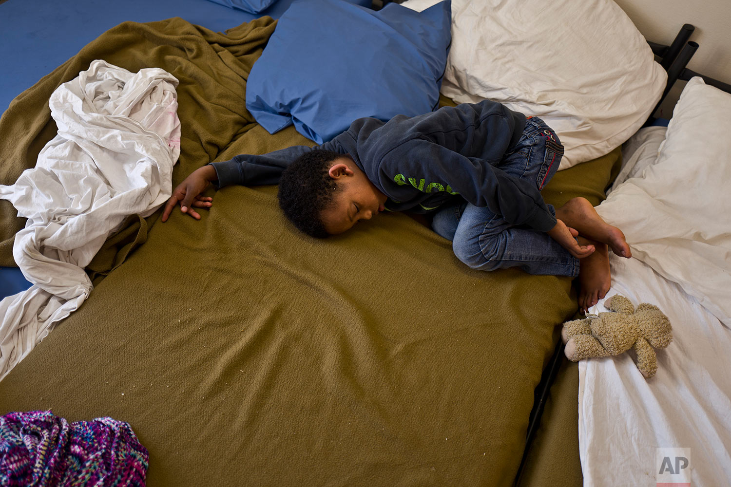In this Friday, July 7, 2017 photo, Eritrean migrant Solomun Drat, 7, sleeps on a bed at his family's room in the former prison of Bijlmerbajes in Amsterdam, Netherlands. (AP Photo/Muhammed Muheisen)