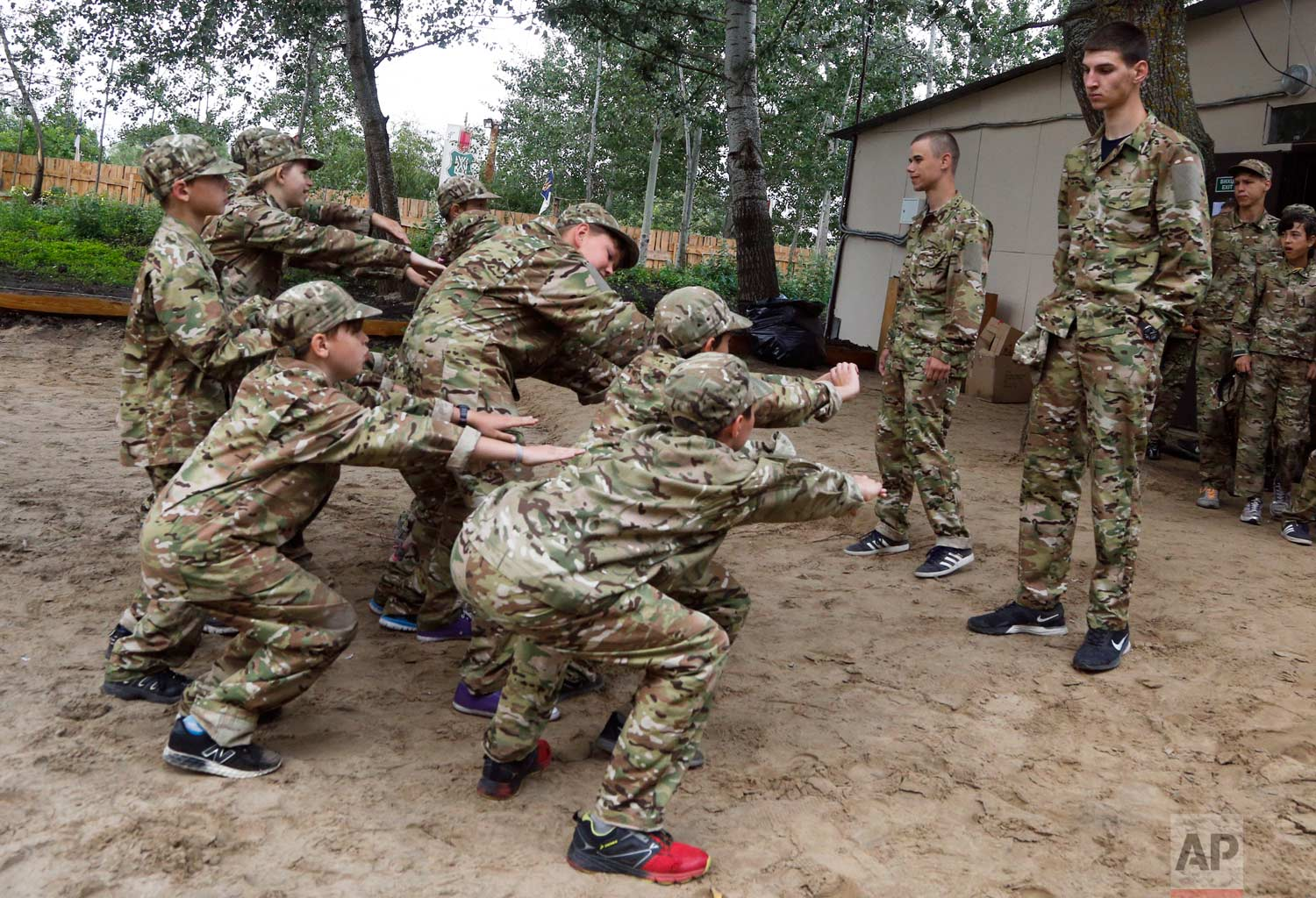 In this photo taken on Friday, July 14, 2017, students at a paramilitary camp for children do squat-ups outside Kiev, Ukraine. (AP Photo/Efrem Lukatsky)