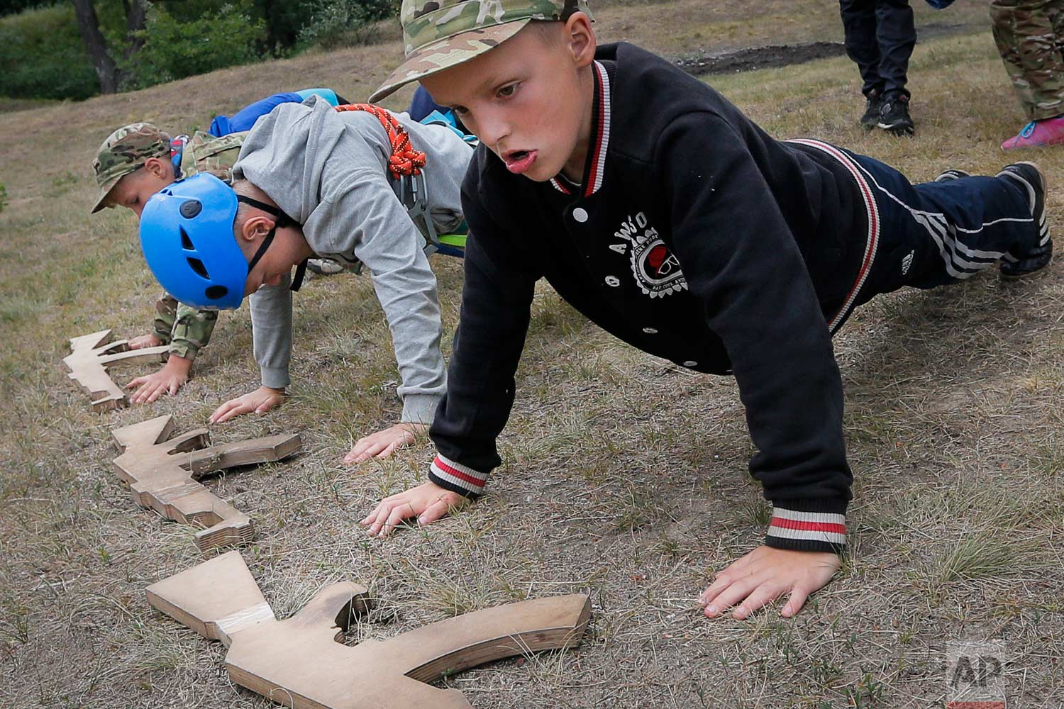 In this photo taken on Friday, July 14, 2017, students at a paramilitary camp for children do push-ups outside Kiev, Ukraine. (AP Photo/Efrem Lukatsky)