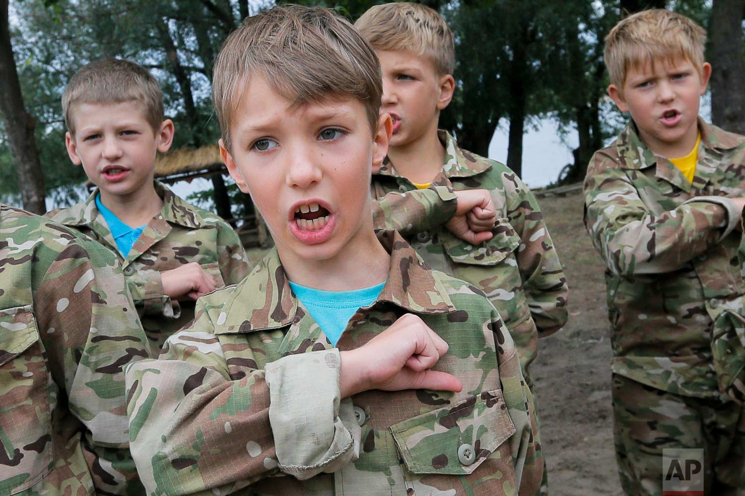 In this photo taken on Friday, July 14, 2017, students at a paramilitary camp for children sing the Ukrainian national anthem before the start of exercises outside Kiev, Ukraine. (AP Photo/Efrem Lukatsky)