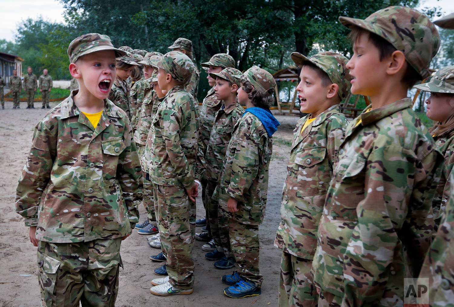 In this photo taken on Friday, July 14, 2017, a student at a paramilitary camp for children calls the rank to attention outside Kiev, Ukraine. (AP Photo/Efrem Lukatsky)