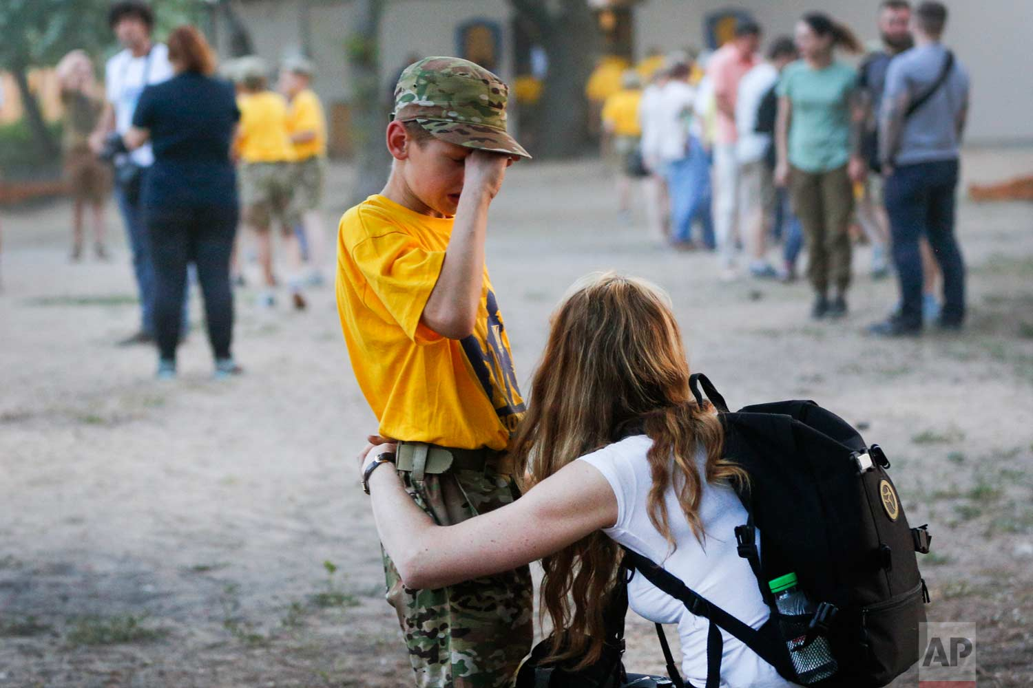 In this photo taken on Saturday, July 8, 2017, a visiting mother consoles her child at a paramilitary camp for children outside Kiev, Ukraine. (AP Photo/Efrem Lukatsky)