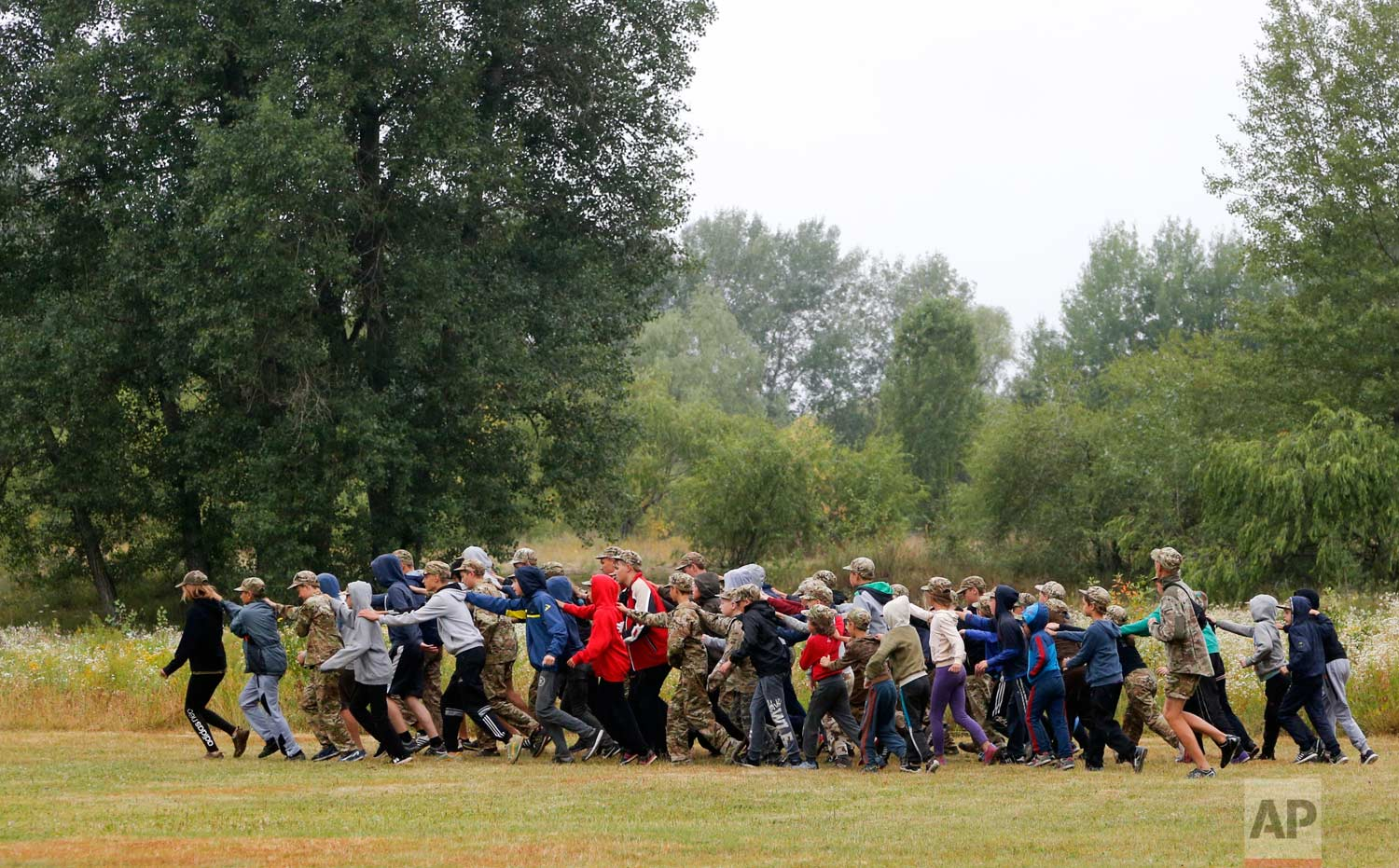 In this photo taken on Friday, July 14, 2017, students at a paramilitary camp for children take part in orientation exercises outside Kiev, Ukraine. (AP Photo/Efrem Lukatsky)