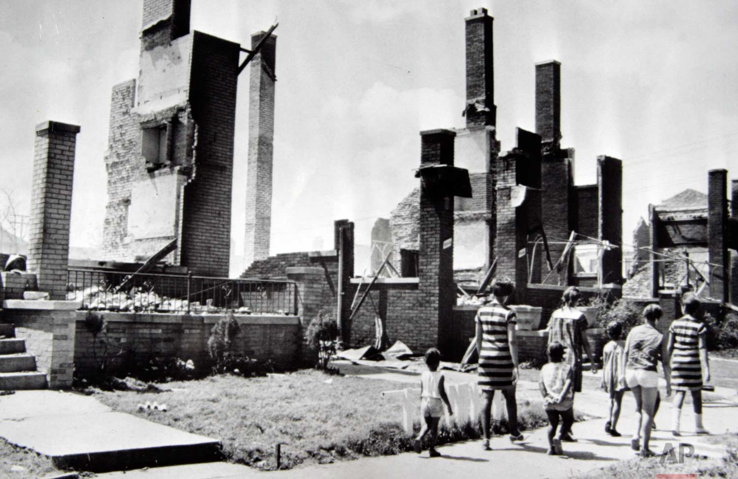 In this July 25, 1967 photo, women and children stroll past the burned remains of homes after riots in Detroit on July 23. The houses were a short distance from 12th Street, center of the riot activity. After the riots, a decline that had already begun would accelerate; Detroit was the nation's fourth biggest city in 1960, but would rank 21st by 2016. The middle class fled, and a proud city fell into poverty, crime and hopelessness. (AP Photo)