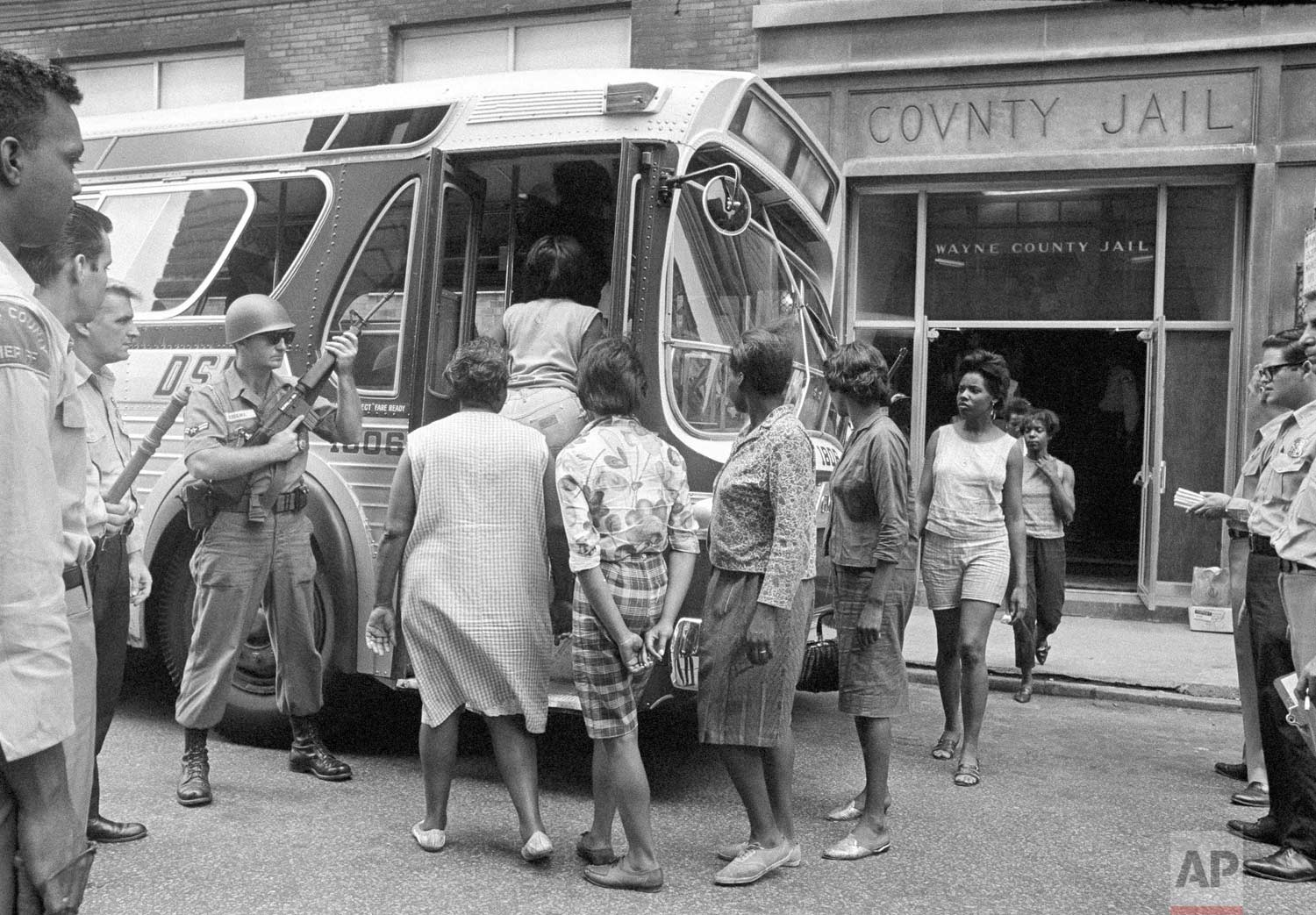 In this July 28, 1967 photo, female prisoners arrested during the rioting in Detroit, board a bus at Wayne County Jail, watched by National Guardsmen for transfer to Eloise, a detention home for women on the edge of the city. Mass arrests of men, women and juveniles had taxed jail facilities in the city. (AP Photo)