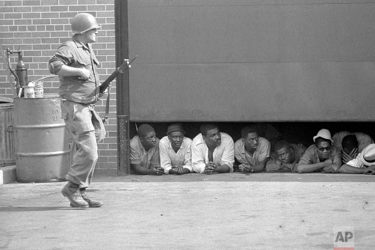 In this July 26, 1967 photo, an Army soldier stands guard as men captured in the vicinity of the 10th Police Precinct in Detroit peer from under a garage door awaiting transfer. The precinct building came under fire in daylight hours and an Army force, using armed personnel carriers and tanks came to the police station. (AP Photo)