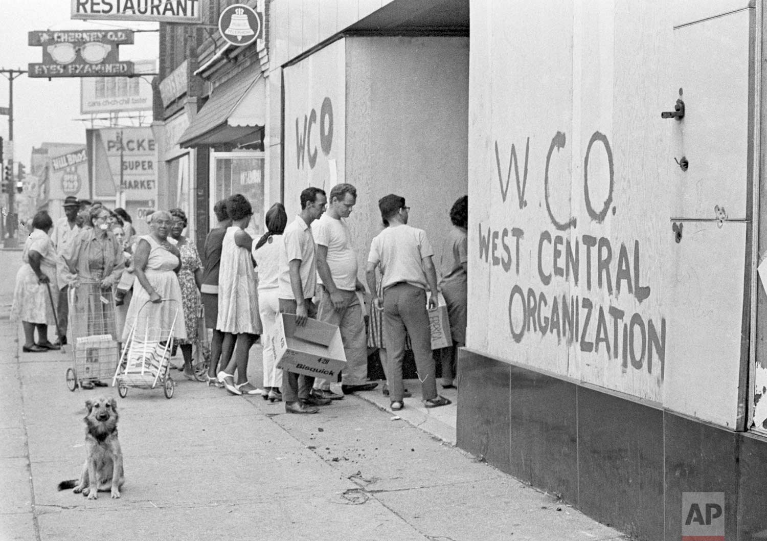 In this July 27, 1967 photo, residents of Detroit's riot area stand in line for free emergency food from a neighborhood organization. Hundreds of grocery stores were burned or looted during the rioting. (AP Photo)