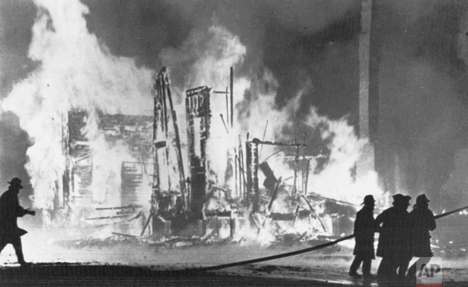 In this July 25, 1967 photo, firefighters try to control blazing buildings after riots in Detroit. Hundreds of fires were reported in the city. Five days of violence would leave 33 blacks and 10 whites dead, and more than 1,400 buildings burned. More than 7,000 people were arrested. (AP Photo)