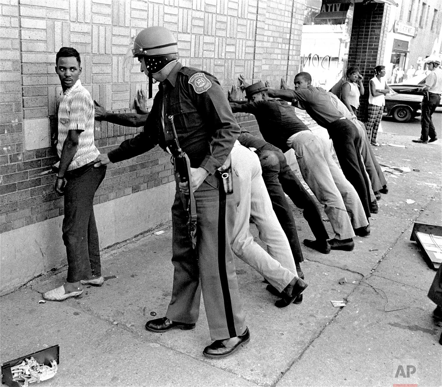 In this July 24, 1967 photo, a Michigan State police officer searches a youth on Detroit's 12th Street where looting was still in progress after the previous day's rioting. The July 23, 1967 raid of an illegal after-hour's club, though, was just the spark. Many in the community blamed frustrations blacks felt toward the mostly white police, and city policies that pushed families into aging and over-crowded neighborhoods. (AP Photo)