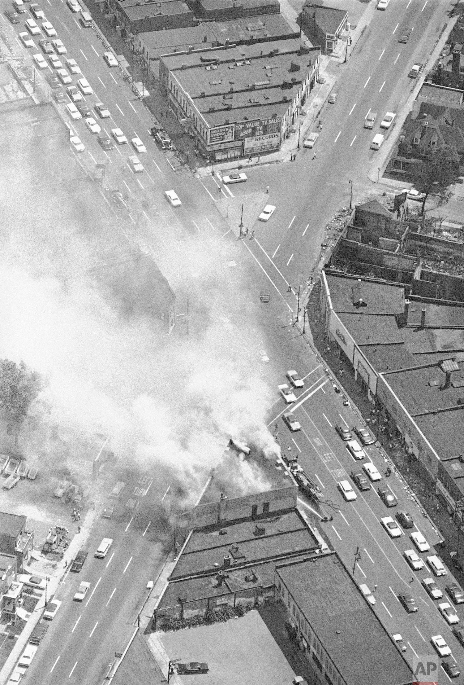 In this July 25, 1967 photo, smoke rises from a fire set at the busy intersection of Grand River and 14 Street in Detroit, near another burned out building. The fire was set despite patrols by the National Guard, police and Army troops. (AP Photo)