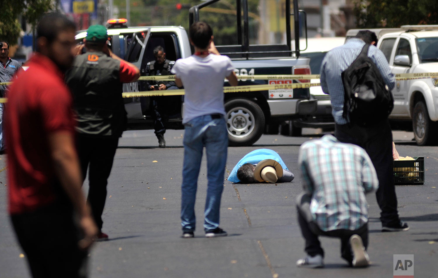 In this May 15, 2017 photo, people take photos of the body of slain journalist Javier Valdez, in Culiacan, Mexico. Mexico is now the world's most lethal country for journalists, more even than war-torn Syria; their murderers are not brought to justice, despite a law passed in 2012 making it a federal crime to kill a journalist. It's never successfully been used to convict a killer. (AP Photo/Fernando Brito)