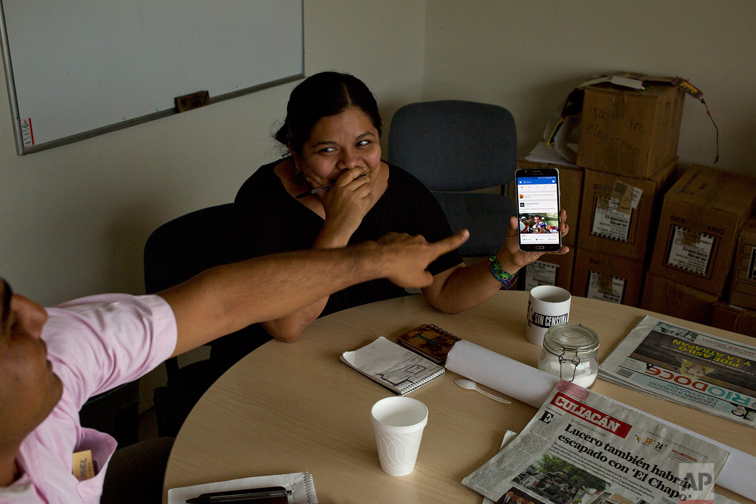 In this June 26 2017 photo, reporter Miriam Ramirez shows a picture on her cellphone to a co-worker during a Riodoce editorial meeting in Culiacan, Sinaloa state, Mexico. After the killing of Riodoce co-founder Javier Valdez on May 15 and with an increase in killings of journalists nationwide, the paper's reporters are told by security experts that, among other things, it's important to change their routines, be more careful with social media and not leave colleagues alone in the office at night. (AP Photo/Enric Marti)