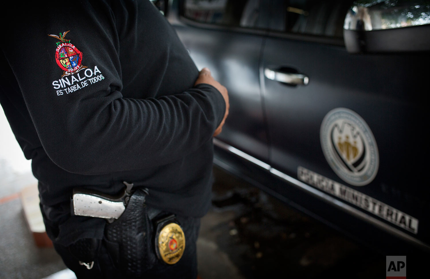 """In this June 28, 2017 photo, a police officer stands outside Riodoce's office in Culiacan, Sinaloa state, Mexico. After the killing of Riodoce co-founder Javier Valdez, two police were assigned by the state government to guard the newspaper's offices. Half-jokingly, some of the reporters wondered whether these officers are among the 50 percent of cops whom the governor himself has said are not trustworthy. The badge on the police officer's sleeve reads, in Spanish, """"Sinaloa is everyone's task."""" (AP Photo/Enric Marti)"""