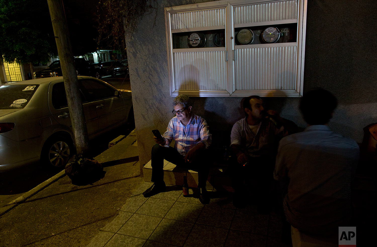 In this June 27, 2017 photo, a family from the United States visits the shrine of Jesus Malverde, the so-called narco-saint revered by many of Mexico's drug traffickers, in Culiacan, Sinaloa state, Mexico. In Sinaloa people are shot dead in the street every day and the cemetery is filled with ornate, two-story mausoleums for drug kings that are larger than many homes for the living. (AP Photo/Enric Marti)