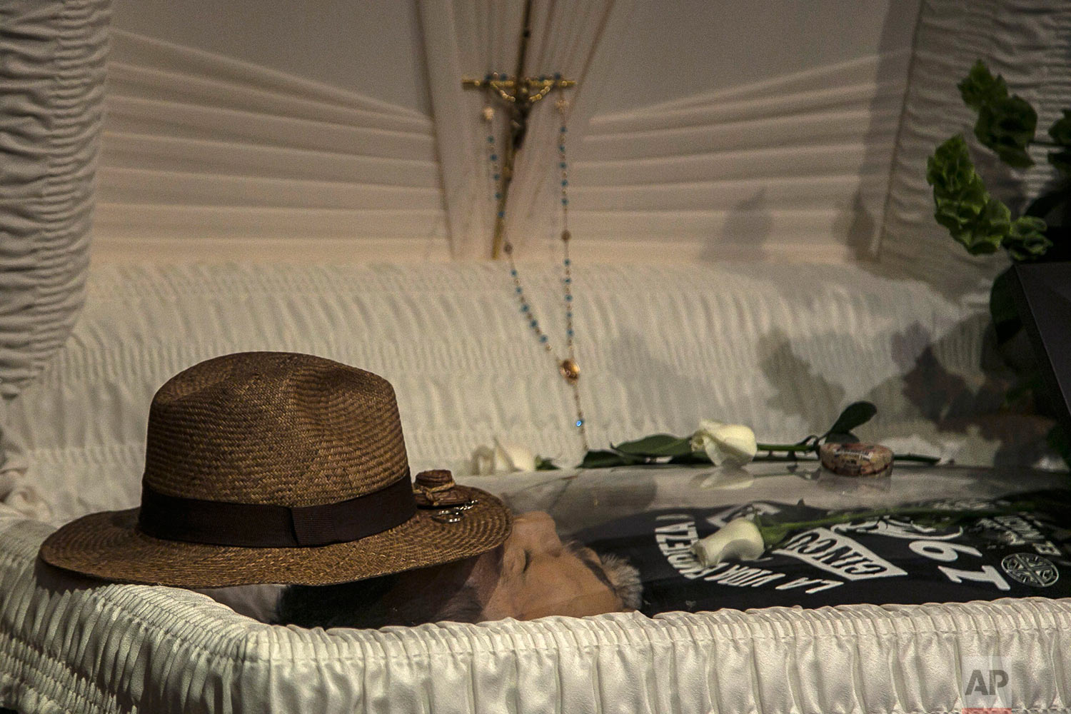 """In this May 16, 2017 photo, the hat of slain journalist Javier Valdez lays on his forehead inside a funeral home before his wake begins in Culiacan, Mexico. """"The greatest error is to live in Mexico and to be a journalist,"""" wrote Valdez, a legend in Mexico and abroad, whose killing is seen as a milestone in Mexican violence against journalists. Valdez, 50, left a wife and two adult children. There have been no arrests _ which is no surprise to the national press corps. (AP Photo/Rashide Frias)"""