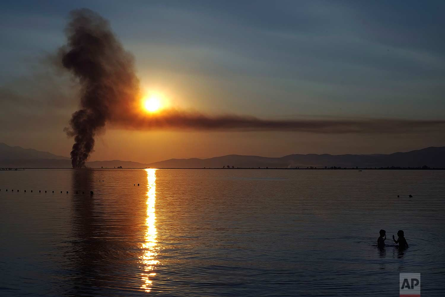 Children play in the sea as smoke from a fire rises in the background during a sunset at Keramoti, northern Greece, on Sunday, July 30, 2017. (AP Photo/Petros Karadjias)