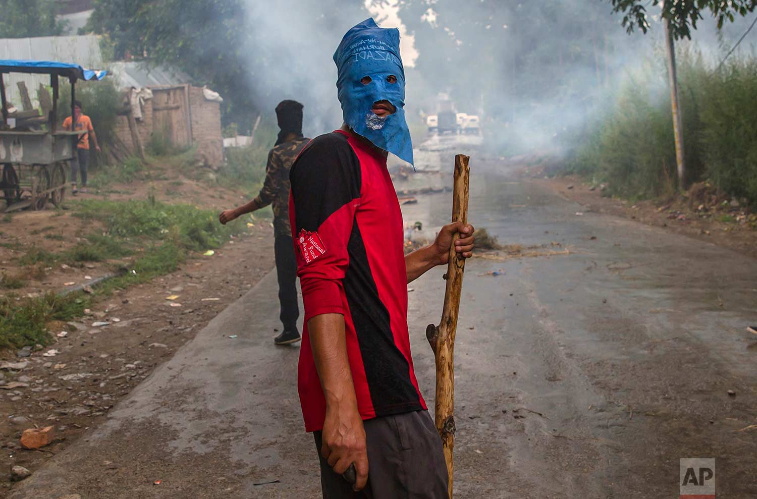 A masked villager holds a wooden stick and stones during a protest following the funeral procession of Akeel Ahmed Bhat, a teenage boy in Haal village, about 47 kilometers (29 miles) south of Srinagar, Indian controlled Kashmir, Wednesday, Aug. 2, 2017. (AP Photo/Dar Yasin)