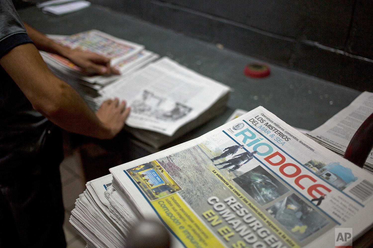 """In this July 1, 2017 photo, workers fold an issue of the weekly Riodoce after it was printed in Culiacan, Sinaloa state, Mexico. Riodoce was created in 2003 by five local journalist including the late Javier Valdez selling $50 shares. In Sinaloa, """"it was impossible to do journalism without touching the narco issue,"""" said director and co-founder Ismael Bojorquez. Over time the paper earned a reputation for brave and honest coverage. (AP Photo/Enric Marti)"""