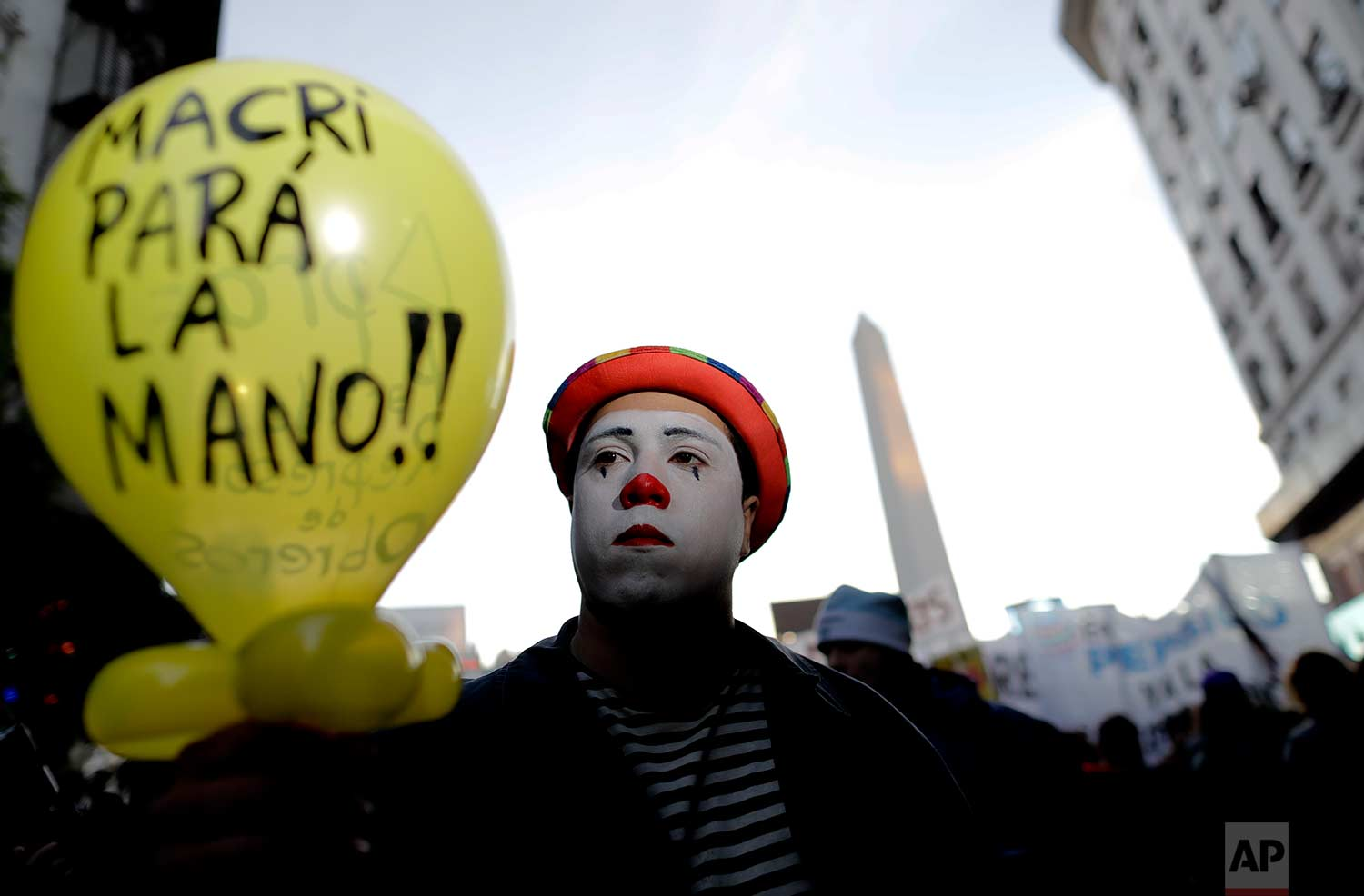 """A clown marches with a balloon with text written in Spanish that reads """"Macri, take it easy,"""" in Buenos Aires, Argentina, Tuesday, July 18, 2017. (AP Photo/Natacha Pisarenko)"""