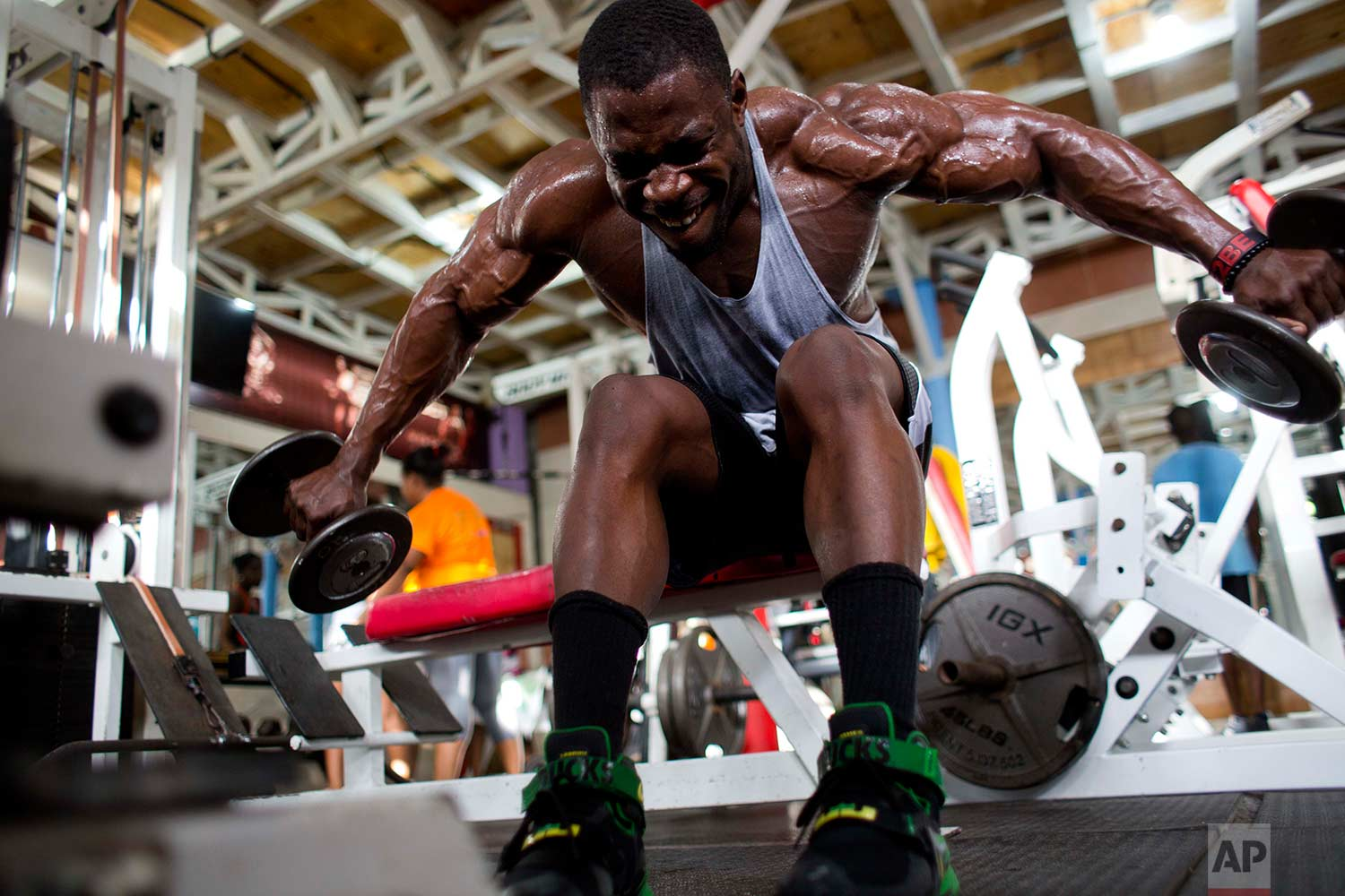 In this July 20, 2017 photo, bodybuilder Spely Laventure trains for an upcoming competition between Haiti and Dominican Republic in Port-au-Prince, Haiti. (AP Photo/Dieu Nalio Chery)