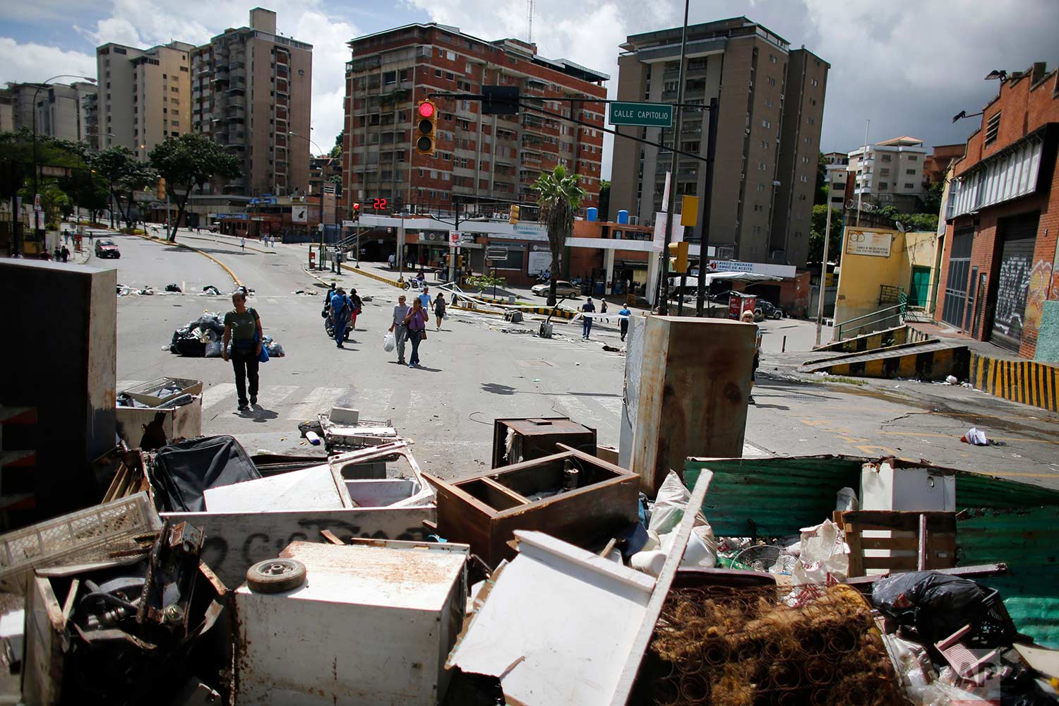 Residents of Petare neighborhood walk near a barricade made by anti-government demonstrators to protest against President Nicolas Maduro's plan to rewrite the constitution in Caracas, Venezuela, Saturday, July 29, 2017. (AP Photo/Ariana Cubillos)