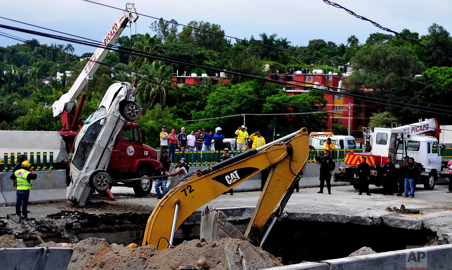 Rescue workers use a crane to lift a vehicle that drove into a sinkhole on a highway in Cuernavaca, Mexico, Wednesday, July 12, 2017. (AP Photo/Tony Rivera)