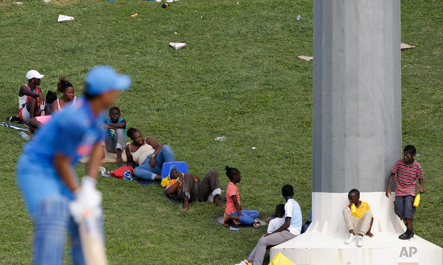 In this July 2, 2017 photo, spectators watch the fourth ODI cricket match between India and West Indies as India's MS Dhoni waits for a delivery at the Sir Vivian Richards Stadium in North Sound, Antigua and Barbuda. (AP Photo/Ricardo Mazalan)