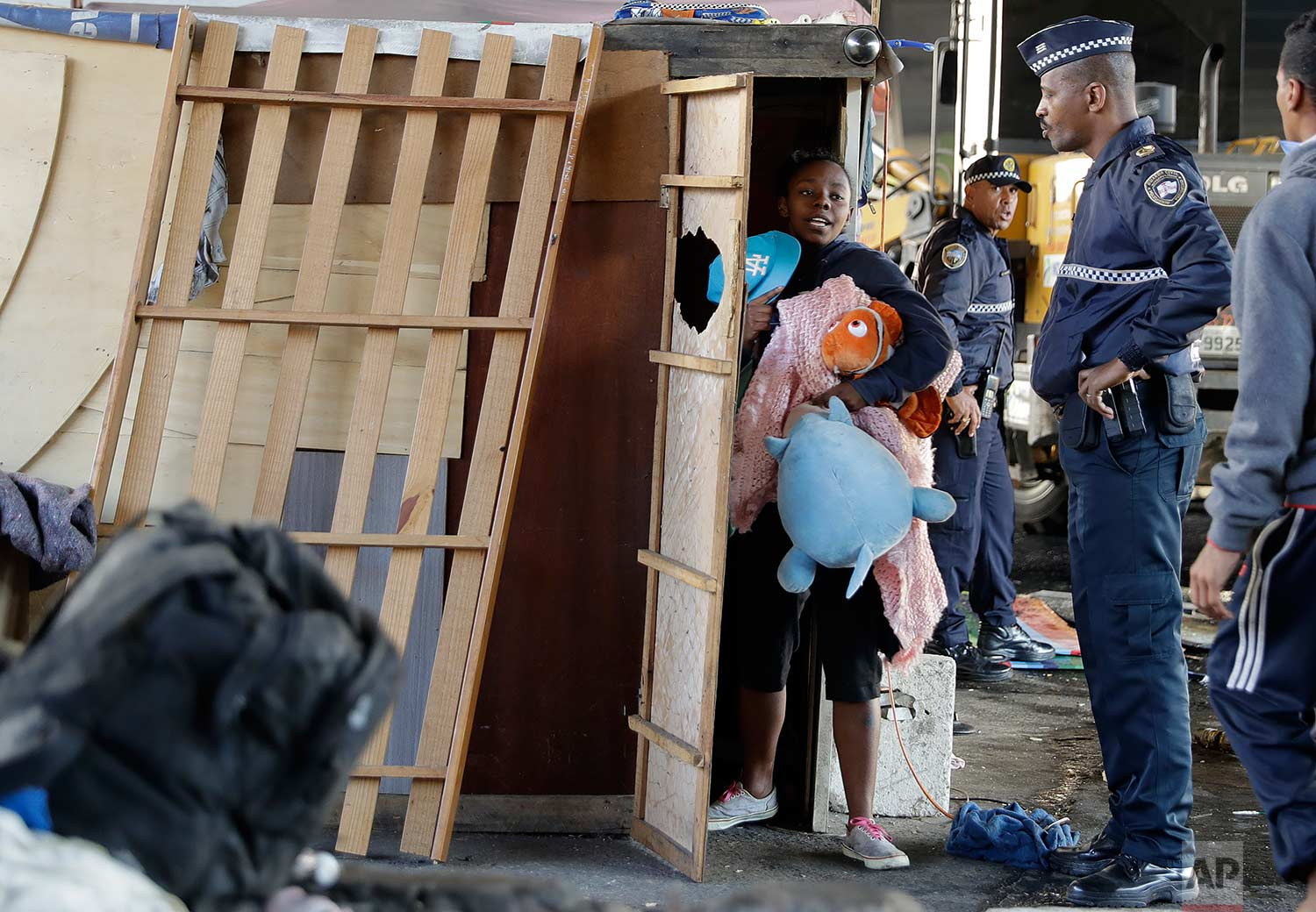 A police officer stands by as a woman carries her belongings during an eviction of people living in shacks beneath an overpass, in Sao Paulo, Brazil, Saturday, July 29, 2017. (AP Photo/Andre Penner)