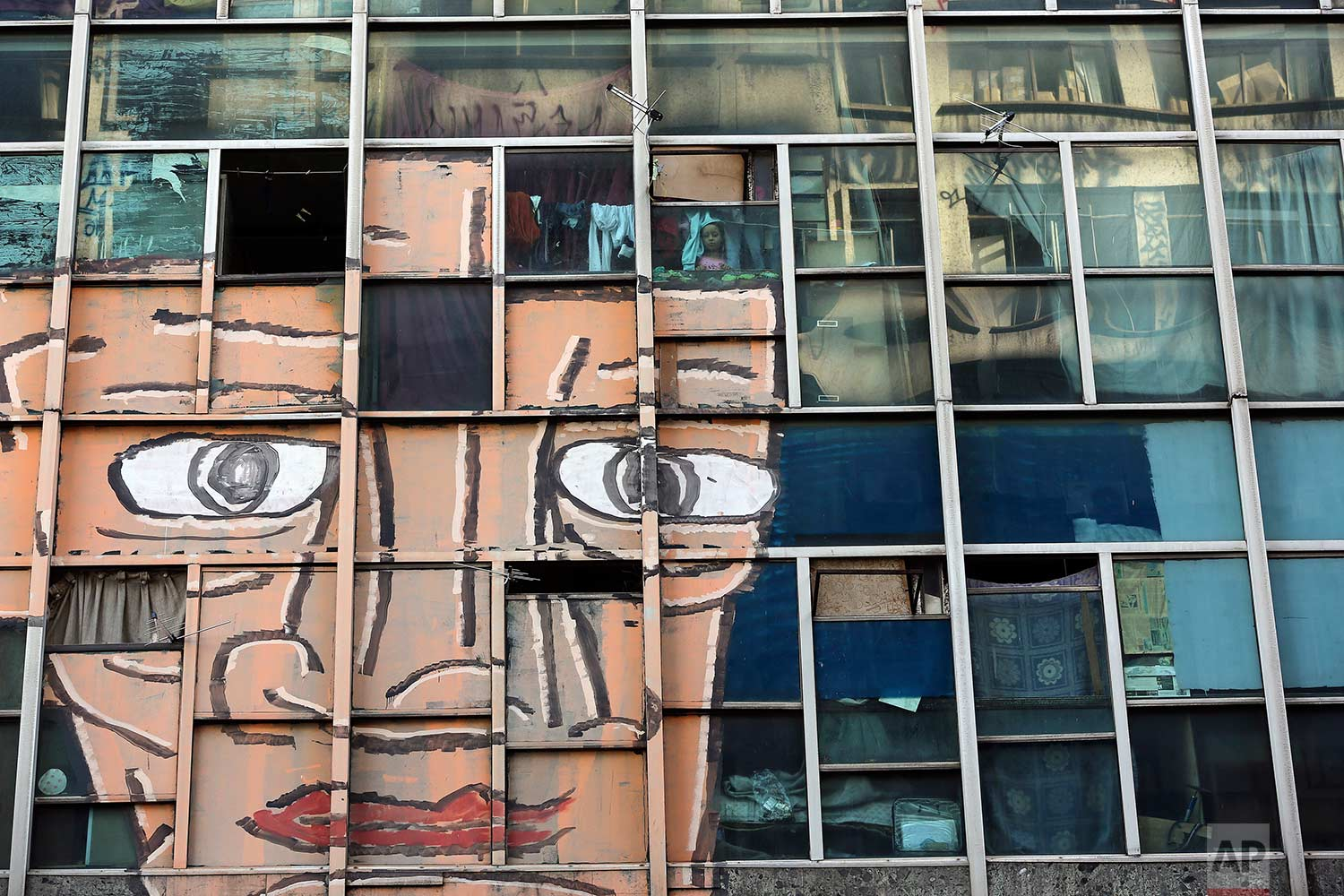 In this June 24, 2017 photo, a girl looks out from her window at the former Federal Police headquarters building in downtown  Sao Paulo, Brazil. (AP Photo/Andre Penner)