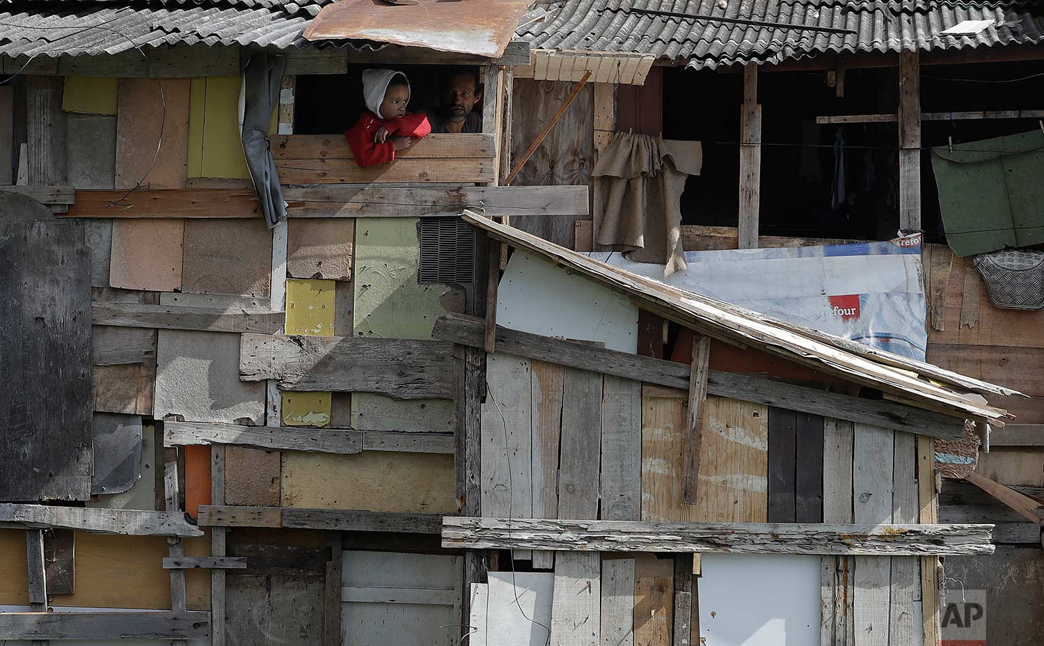 A boy peers from his home's window as firefighters put out the last flames of a nearby fire in Osasco in the greater Sao Paulo area of Brazil, Monday, July 3, 2017.  (AP Photo/Andre Penner)