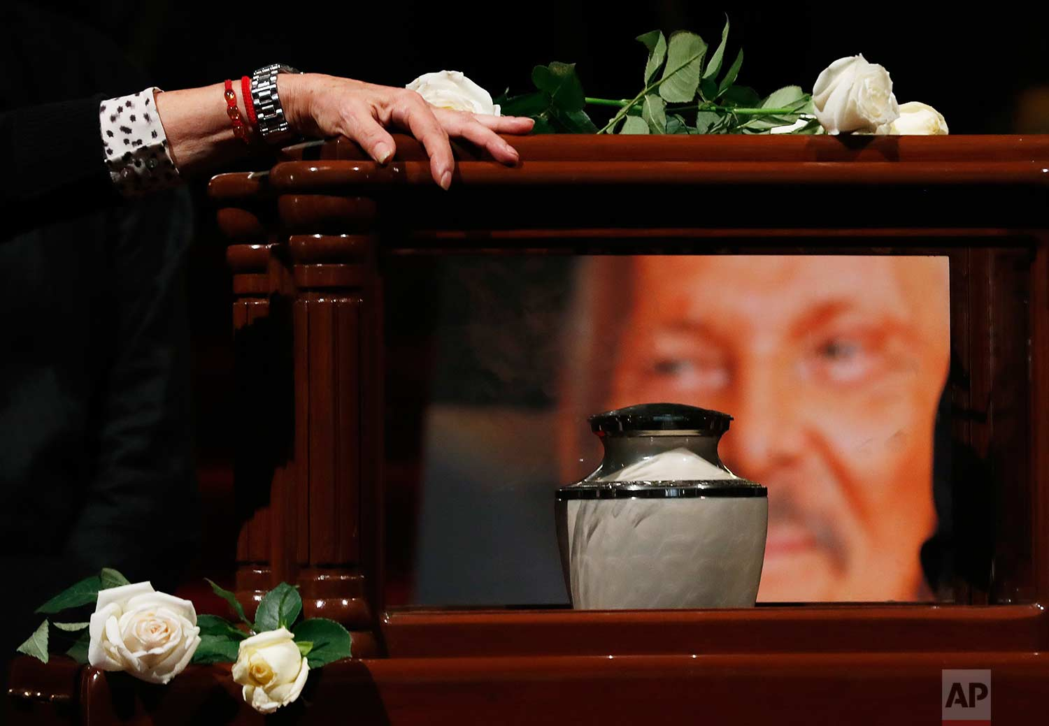 A woman touches the box containing the ashes of of Mexican painter Jose Luis Cuevas, in the Palace of Fine Arts in Mexico City, Tuesday, July 4, 2017. (AP Photo/Eduardo Verdugo)