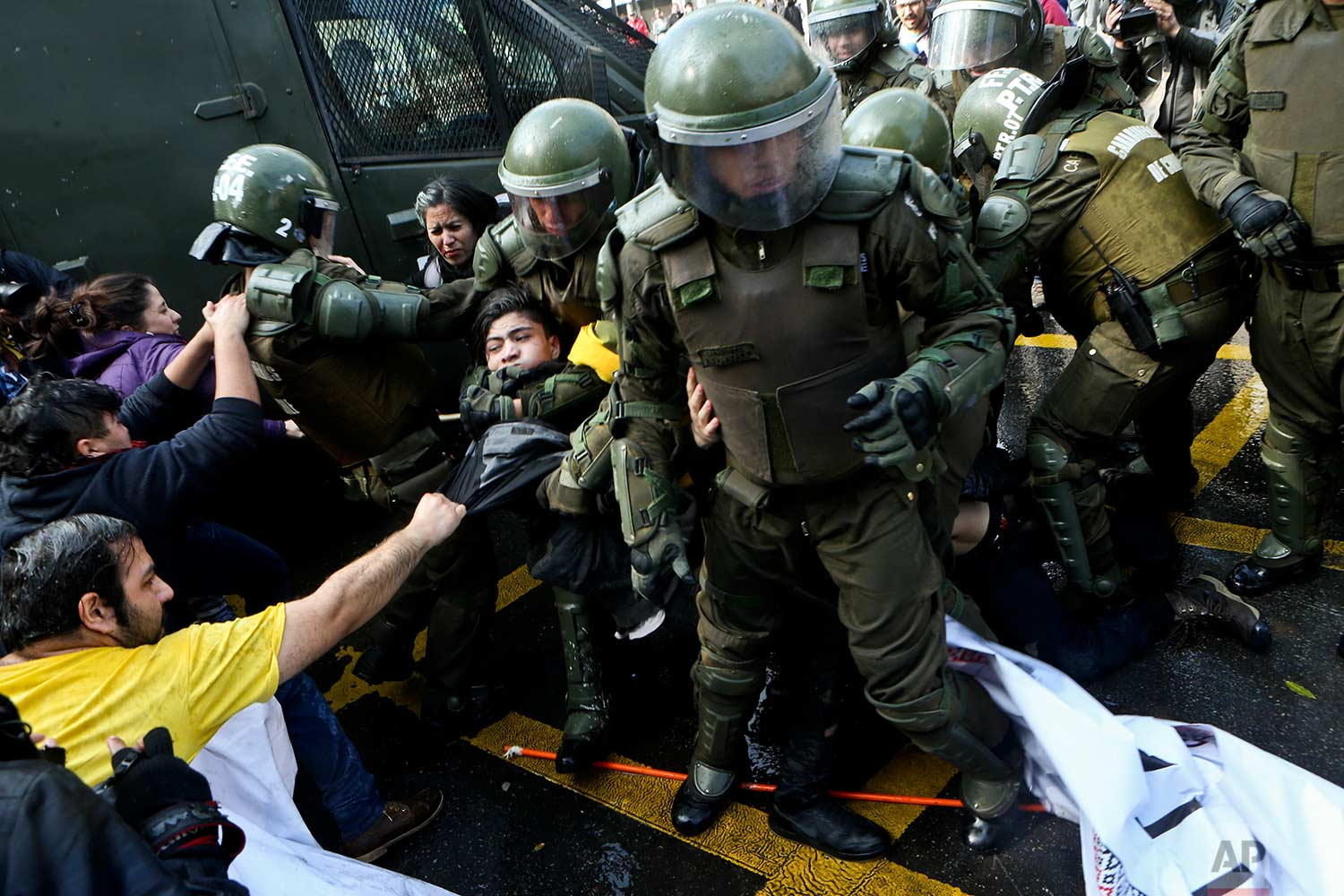 Police break up a protest, that was blocking a street, demanding an end to the current Pension Fund Administrators (AFP) system in Santiago, Chile, Monday, July 24, 2017. (AP Photo/Esteban Felix)
