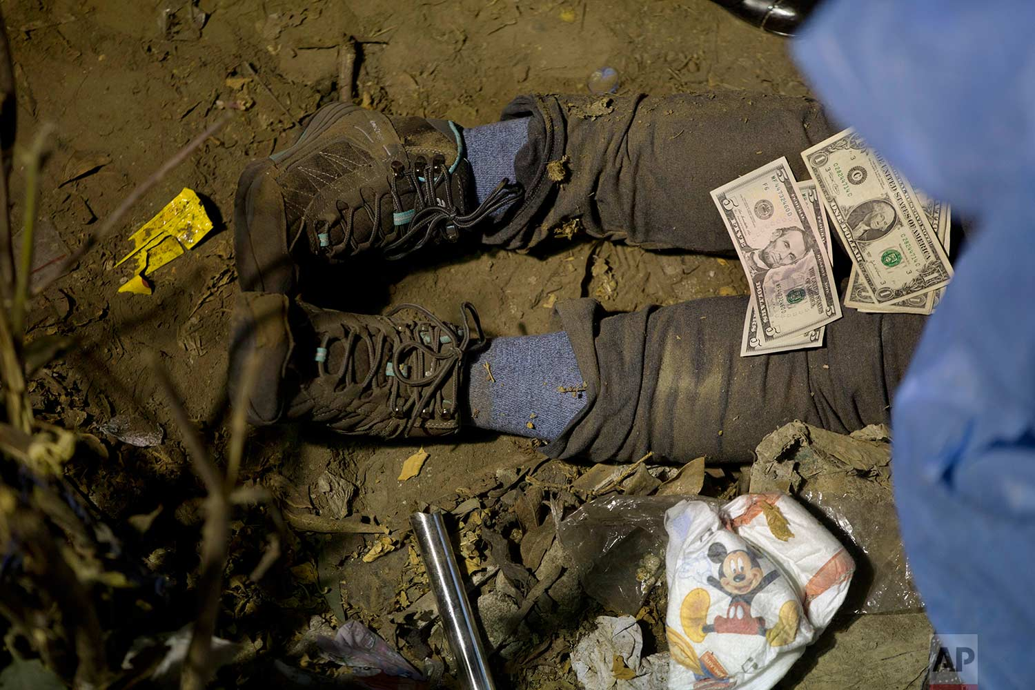 Bills of U.S. dollars are placed over the body of a tourist after they were found in pockets of her clothes as rescue workers and policemen work the scene of a deadly bus accident in Lima, Peru, Sunday, July 9, 2017. (AP Photo/Rodrigo Abd)