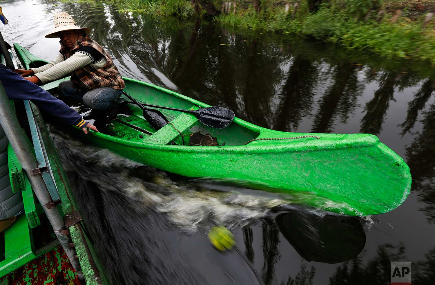 """In this July 13, 2017 photo, a farmer takes advantage of a motorized boat to move faster along the channels of Xochimilco to his floating farm known as a """"chinampa"""" in Mexico City. (AP Photo/Marco Ugarte)"""