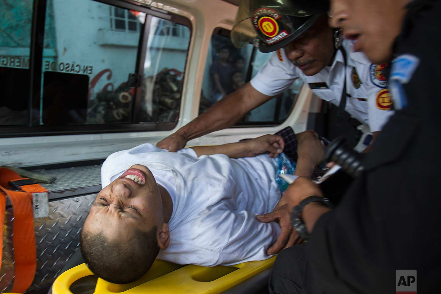A juvenile inmate is attended by a medic and interrogated by a police officer, after he was injured during the recapture of the Juvenile Correctional Center Gaviotas by police, in Guatemala City, Monday, July 3, 2017. (AP Photo/Moises Castillo)