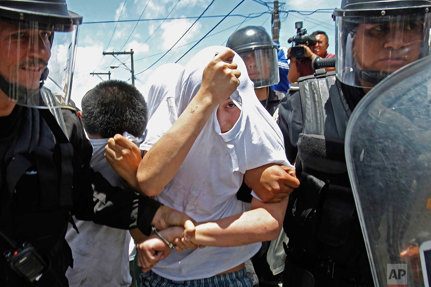 National Civil Police Special Forces escort recaptured inmates from the Juvenile Correctional Center Gaviotas in Guatemala City, Monday, July 24, 2017. (AP Photo/Moises Castillo)