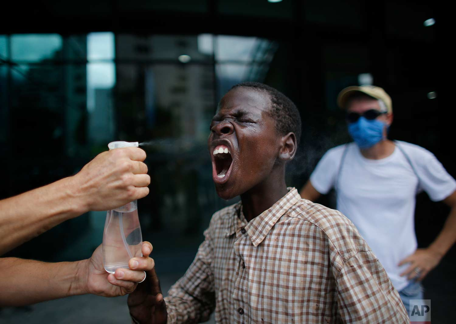 A youth has his face rinsed from the effects of tear gas after security forces lobbed tear gas at demonstrators sheltering inside a shopping mall during a protest march in Caracas, Venezuela, Thursday, July 6, 2017. (AP Photo/Ariana Cubillos)