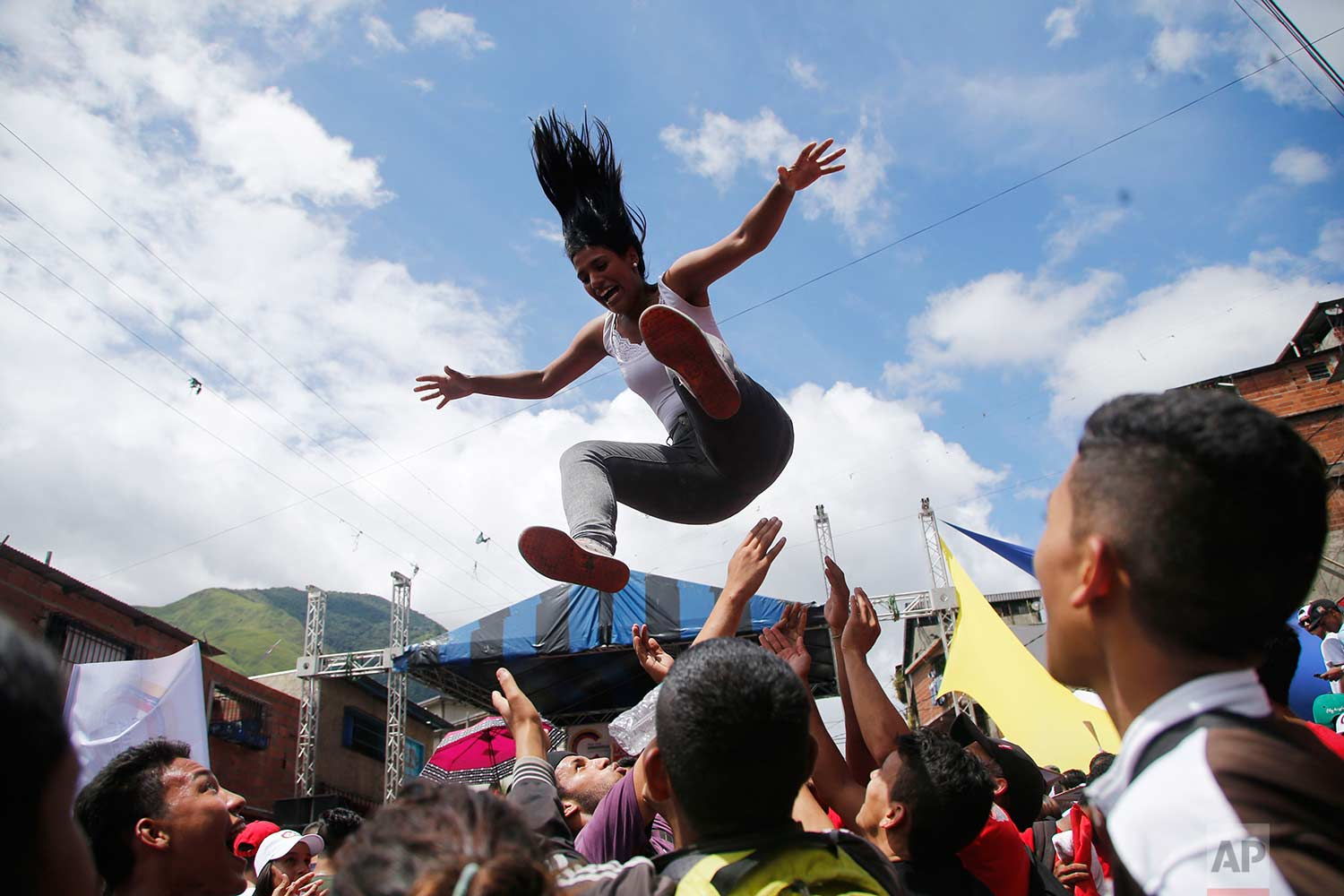 A woman is launched into the air during a pro-government candidates' rally in Caracas, Venezuela, Tuesday, July 25, 2017. (AP Photo/Ariana Cubillos)