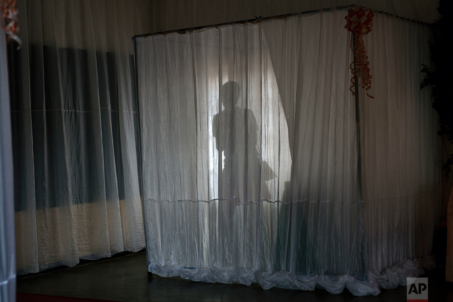 A Rwandan woman exits the booth before casting her election vote in Rwanda's capital Kigali Friday Aug. 4, 2017. Rwandans voted in an election Friday that the country's longtime president is widely expected to win, after the government disqualified all but three candidates. (AP Photo/Jerome Delay)