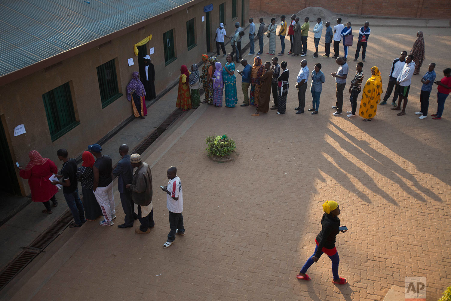 Rwandans line up to cast their vote for the presidential elections at a polling station in Rwanda's capital Kigali Friday, Aug. 4, 2017. Outgoing President Paul Kagame is widely expected to win another term after the government disqualified all but three candidates. (AP Photo/Jerome Delay)