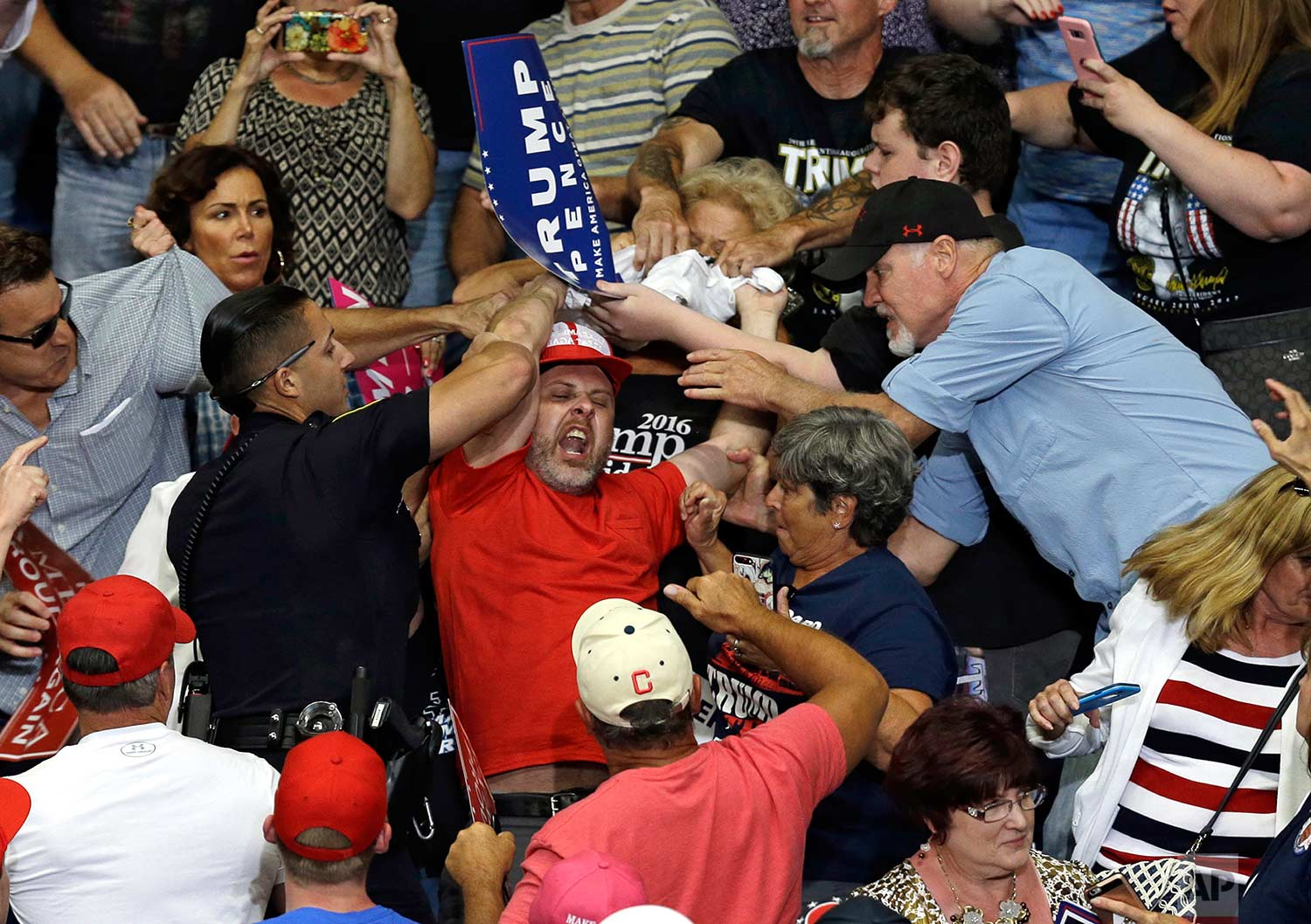 A protester is escorted out of the Covelli Centre during a rally as President Donald Trump speaks, Tuesday, July 25, 2017, in Youngstown, Ohio. (AP Photo/Tony Dejak)