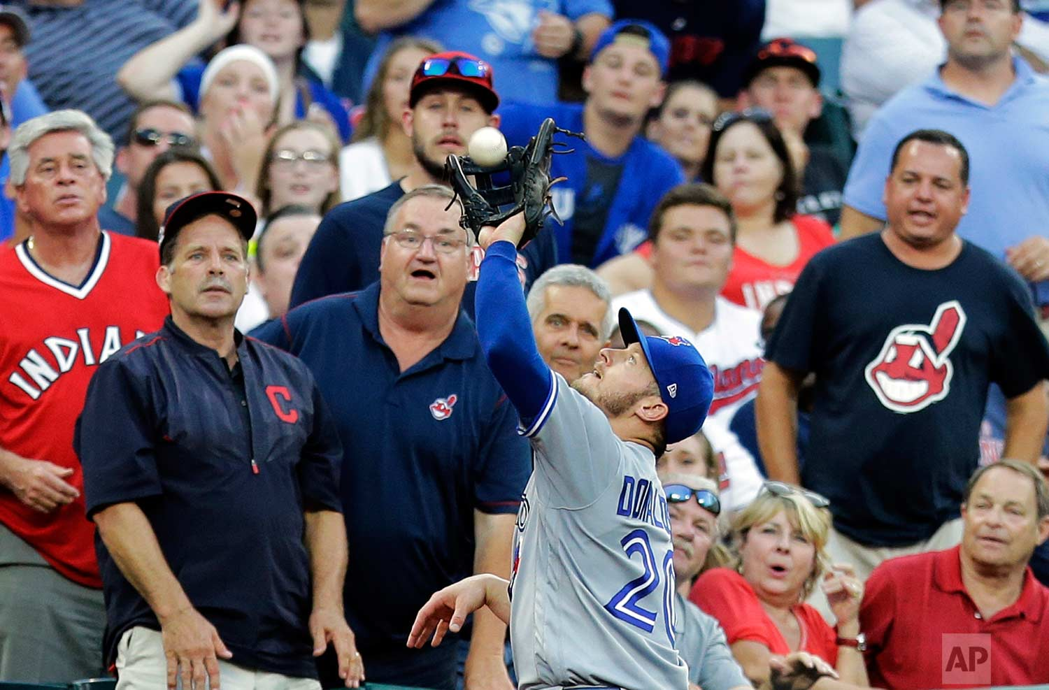 Toronto Blue Jays' Josh Donaldson (20) catches a foul ball by Cleveland Indians' Abraham Almonte in the fifth inning of a baseball game, Saturday, July 22, 2017, in Cleveland. (AP Photo/Tony Dejak)