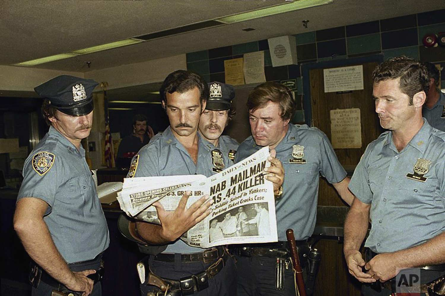 "Unidentified officers of the 84th Precinct in Brooklyn read news of the capture of the "".44 Caliber Killer"", David Berkowitz, Aug. 11, 1977. (AP Photo/Dan Goodrich)"